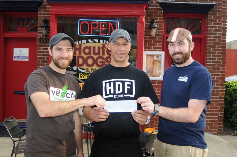 volunteer coordinators Joe and Kyle receiving check from Haute Dogs owner Lionel.