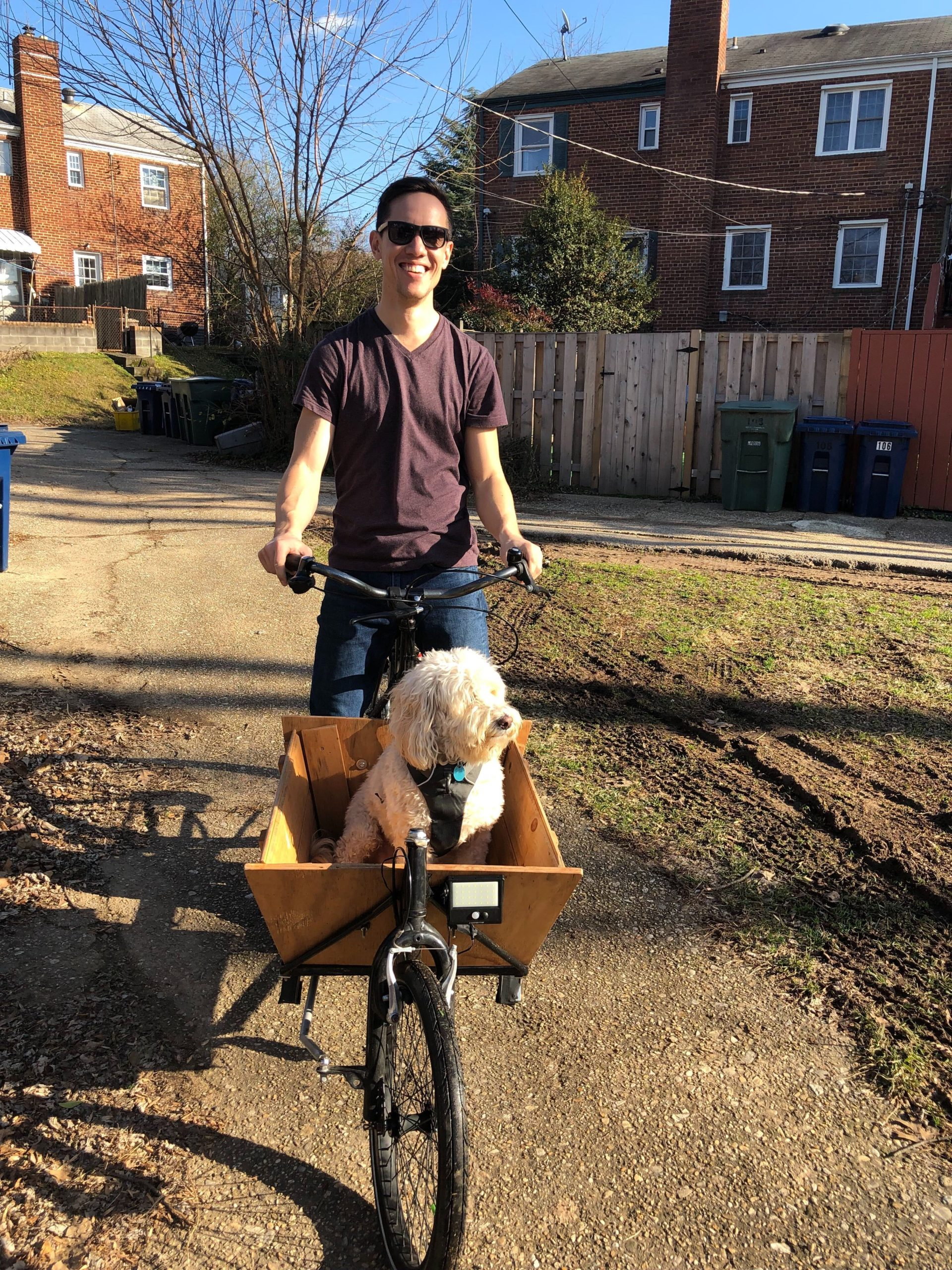 Victor Yaguchi on a front loading cargo bike with a dog
